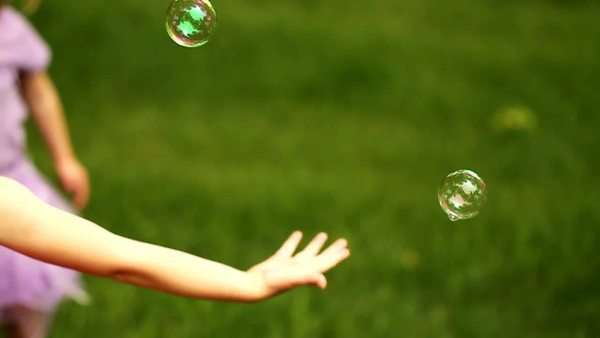 Young girl pops floating bubble outside Royalty-free stock video