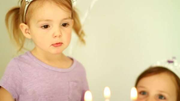 Young girls celebrating, girl blows out candles Royalty-free stock video