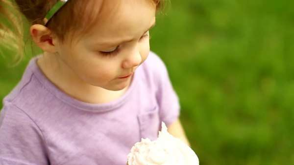Little girl licks icing off cupcake Royalty-free stock video