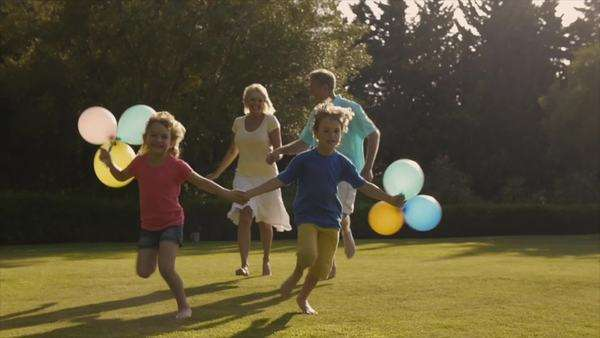 Grandchildren and grandparents running to camera in garden holding balloons. Royalty-free stock video