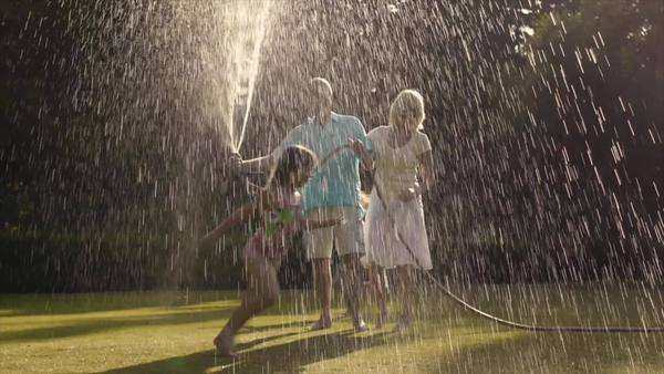 Grandchildren and grandparents in garden playing with water spray. Royalty-free stock video