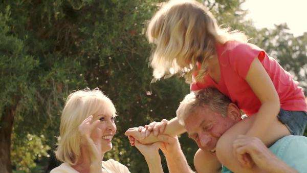 Grandparents and granddaughter playing on grandfathers shoulders in garden. Royalty-free stock video