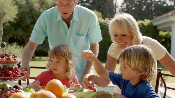 Grandparents and grandchildren walking to table of food in garden. Royalty-free stock video