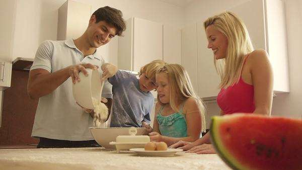 Medium dolly shot of family baking in kitchen. Royalty-free stock video