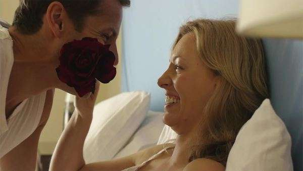 Playful couple in bed with rose. Royalty-free stock video