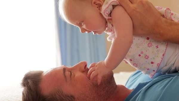 Side view of father on bed with baby daughter. Royalty-free stock video