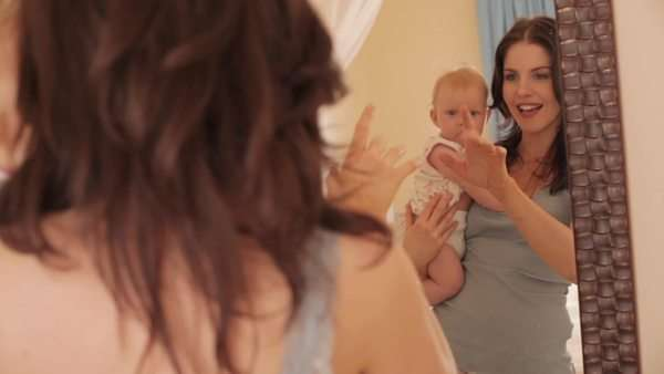 Mother holding baby girl up in mirror. Royalty-free stock video