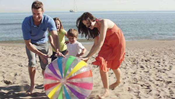 Family on beach rolling beach ball towards camera. Royalty-free stock video