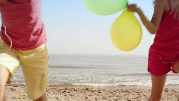 Five children running towards camera on beach holding balloons. Royalty-free stock video