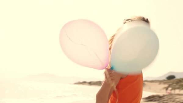 Slow motion of children playing on beach holding balloons. Royalty-free stock video
