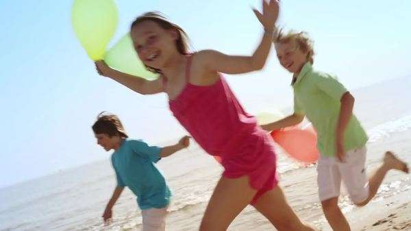 Slow motion of five children running by camera on beach holding balloons. Royalty-free stock video