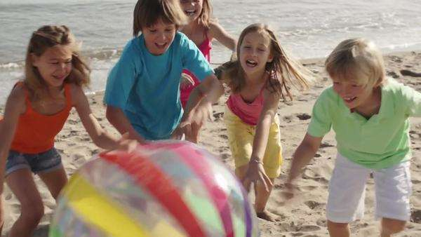 Five children running towards camera on beach pushing beach ball. Royalty-free stock video