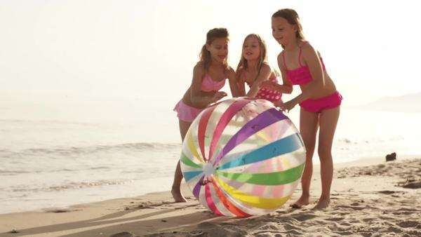 Slow motion of three children pushing beach ball on beach. Royalty-free stock video