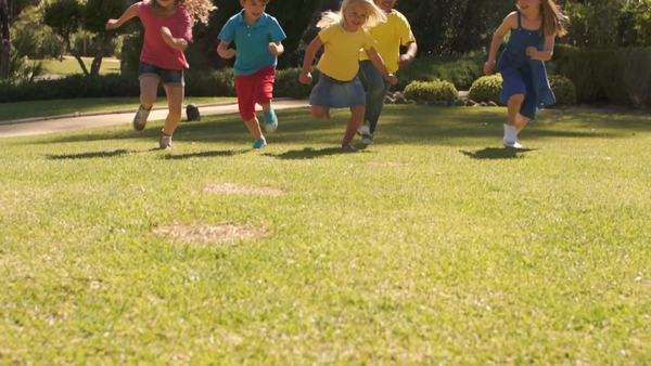 Tilt up slow motion shot of five children running towards camera in park. Royalty-free stock video
