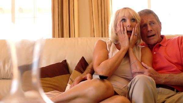 Dolly shot of senior couple watching television on sofa together. Royalty-free stock video