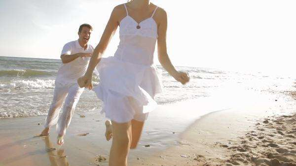 hand held shot of young couple running and chasing on beach Royalty-free stock video