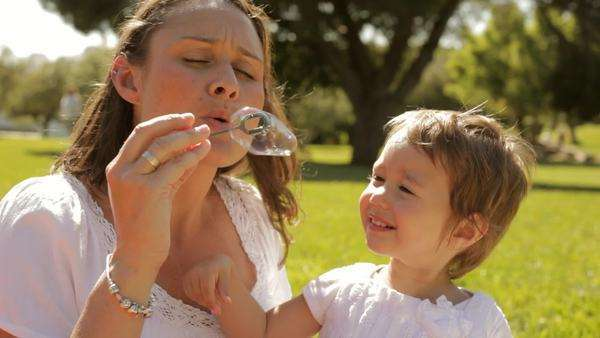 mother and baby playing with bubbles in park Royalty-free stock video