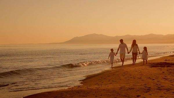 family walking towards camera on beach in sunset Royalty-free stock video