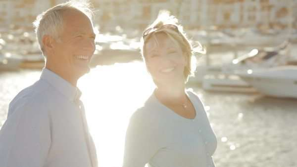 pan shot of senior couple walking by marina in sunset Royalty-free stock video