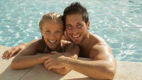 young couple laughing with drinks at side of pool Royalty-free stock video