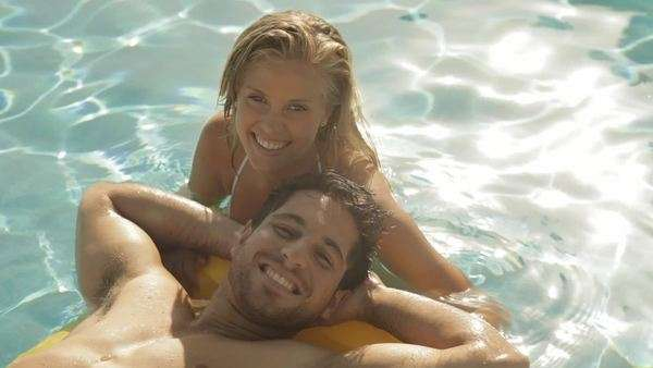 young couple playing and laughing on lilo in pool Royalty-free stock video