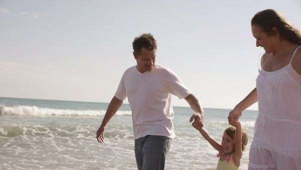 Family walking and swinging daughter on beach. Royalty-free stock video