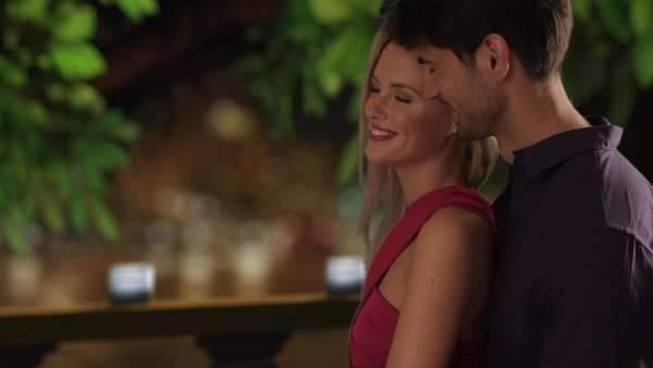 Couple embracing on a balcony at night, cars in background. Royalty-free stock video