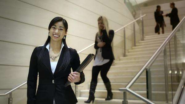 Business people walk up and down the stairs as an asian business woman stops to smile at the camera Royalty-free stock video