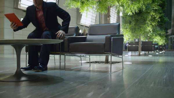 A business man takes a seat in an atrium lobby to look at his ipad Royalty-free stock video