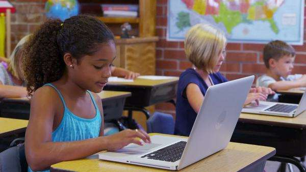 Elementary school students work on laptop computers Royalty-free stock video