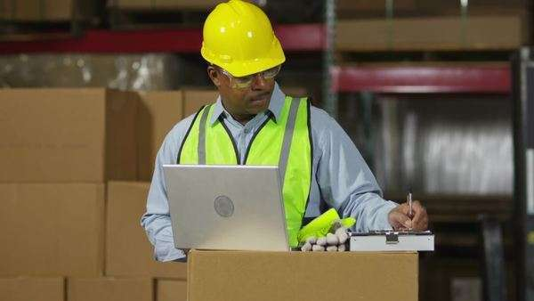 Worker looks at laptop computer in shipping warehouse Royalty-free stock video