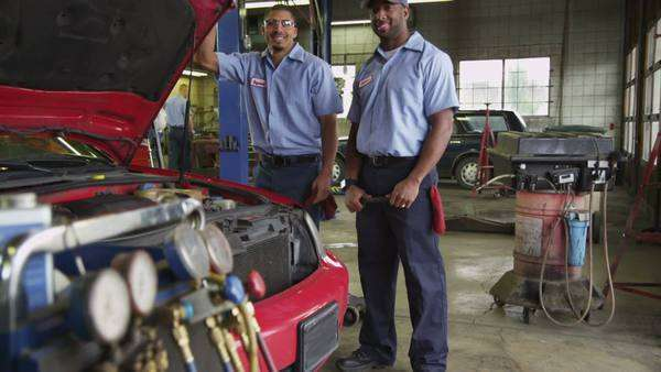 Portrait of two auto mechanics in shop Royalty-free stock video