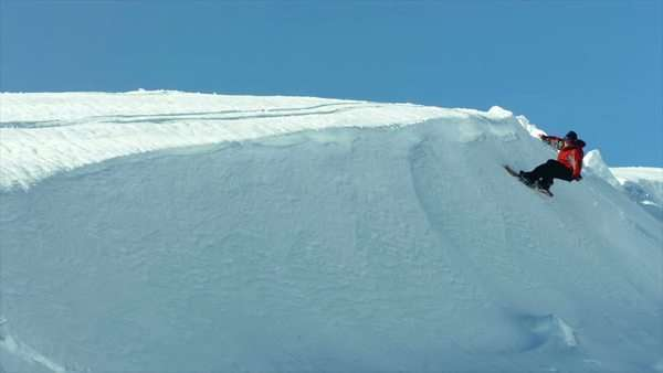 Snowboarder carves snow bank, super slow motion Royalty-free stock video