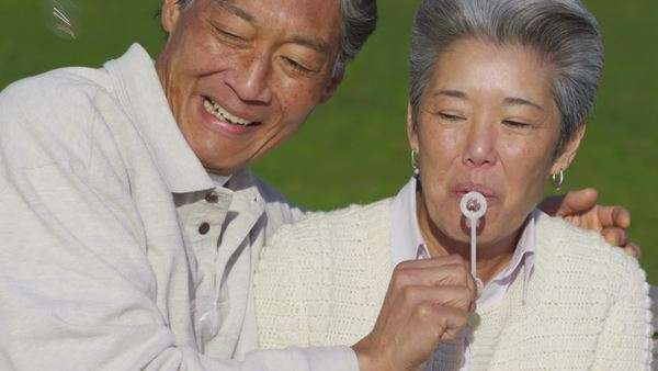 Happy senior couple at park blowing bubbles together Royalty-free stock video