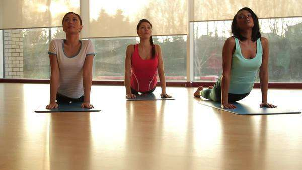 Yoga students practicing yoga in yoga studio Royalty-free stock video