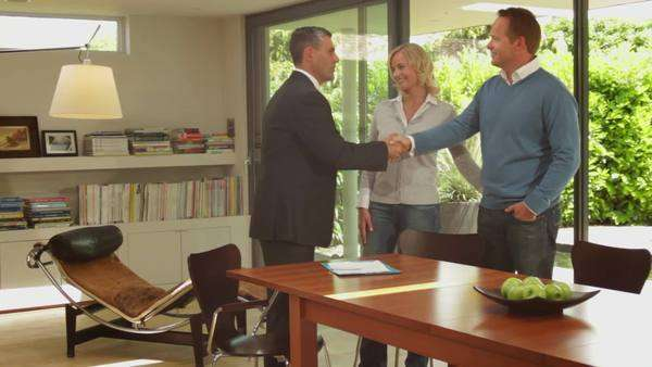Wide shot off couple handshake with sales person in contemporary home Royalty-free stock video