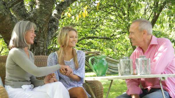 Parenand daughter around table talking in garden Royalty-free stock video