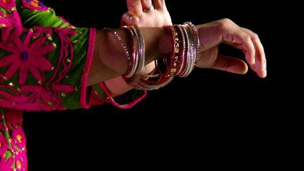 Indian woman in traditional dance costume checks through her wrist bangles  Close up on details with pan from face to arms  Recorded against black background Royalty-free stock video