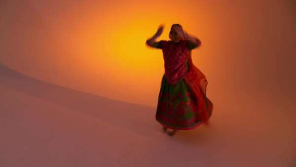 Indian woman in traditional folk costume against an orange colored background with moving camera  Full length shot from raised viewpoint Royalty-free stock video
