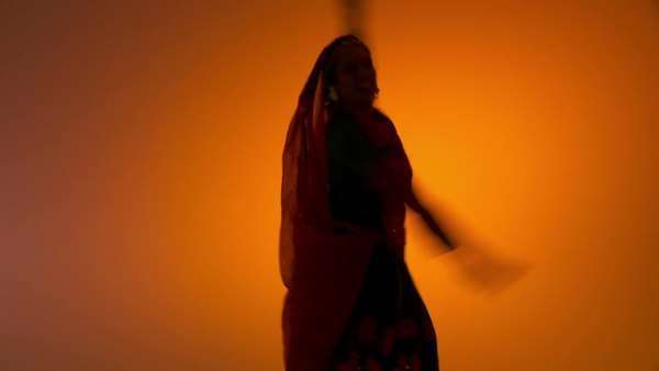 Indian woman in traditional folk costume spins as she dances against an orange colored background with flashing lighting  Hand held camera with various shot sizes Royalty-free stock video