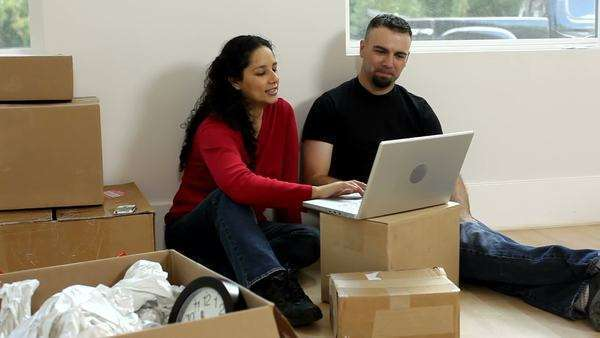 Couple with unpacked boxes looking at laptop Royalty-free stock video