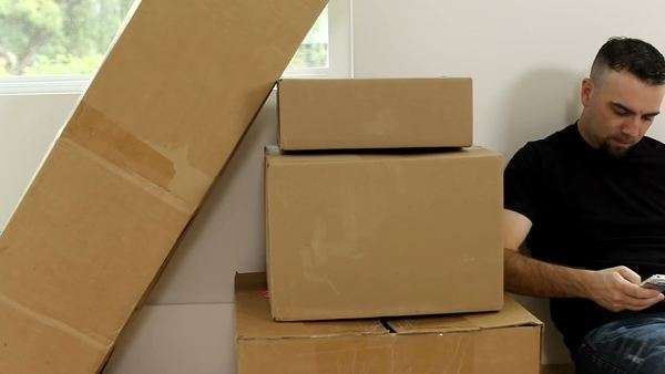 Man sitting by boxes talking on cell phone Royalty-free stock video