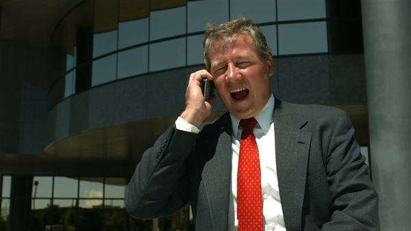 Businessman in front of office building talking on cell phone Royalty-free stock video