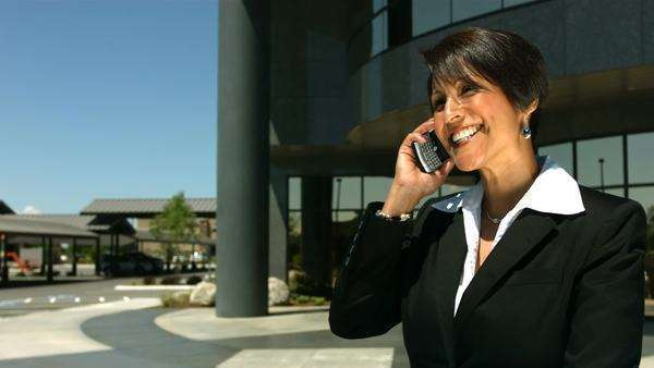 Businesswoman in front of office building talking on cell phone Royalty-free stock video