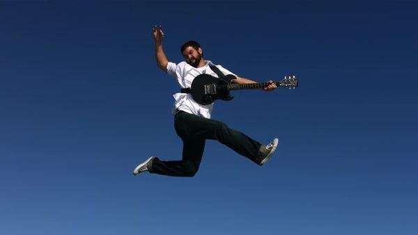 Man jumps into sky playing electric guitar, slow motion Royalty-free stock video