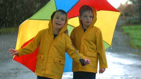 Two young boys in the rain with umbrella, slow motion Royalty-free stock video