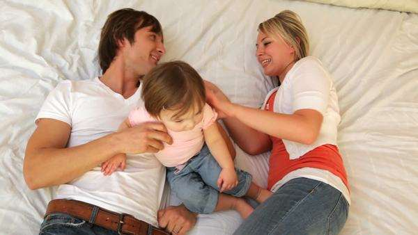 Family with young child playing together on bed Royalty-free stock video