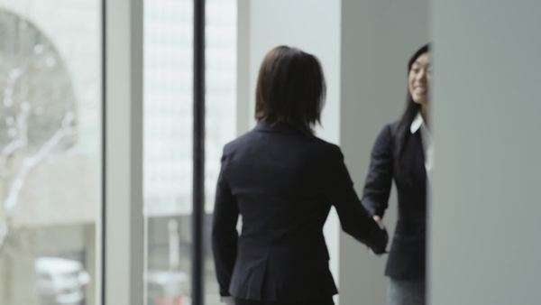 An asian business woman shakes hands as an introduction with another business woman in a large office building Royalty-free stock video