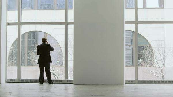 Silhoutte of a man's back making a phone call and talking on his phone in front of a large office window Royalty-free stock video