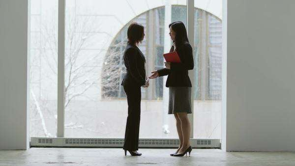 Two young business women stand at a tall window having a conversation Royalty-free stock video